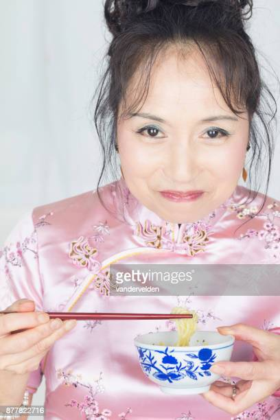 Chinese lady wearing a pink cheongsam eating noodles.