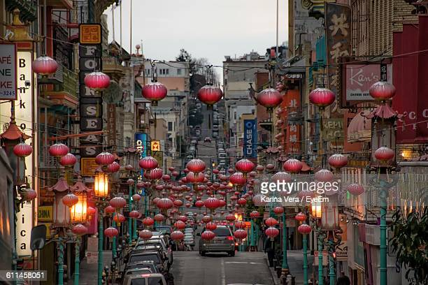 chinese lantern hanging over street amidst buildings in city - chinatown stock pictures, royalty-free photos & images