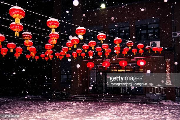 Chinese lanterns illuminated in the snow celebrating for Chinese new year at night.