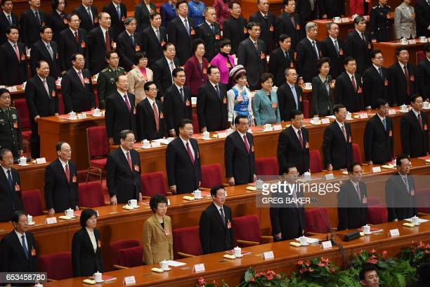 Chinese leaders sing the national anthem during the closing ceremony of the National People's Congress China's rubberstamp legislature in the Great...