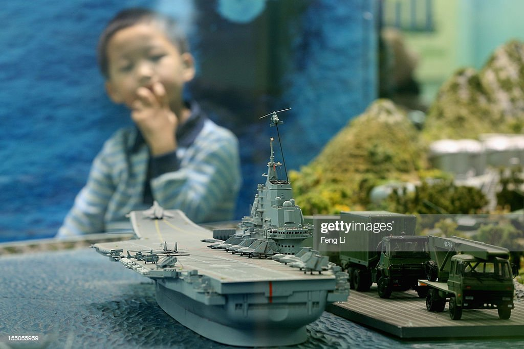 A Chinese little boy looks at the model of China's first aircraft carrier as visiting an exhibition entitled 'Scientific Development and Splendid Achievements' before the18th National Congress of the Communist Party of China (CPC) on October 31, 2012 in Beijing, China. The exhibition showcases China's progress in political, economic, cultural and ecological spheres over the past decade. The18th National Congress of the Communist Party of China (CPC) is proposed to convene on November 8 in Beijing.