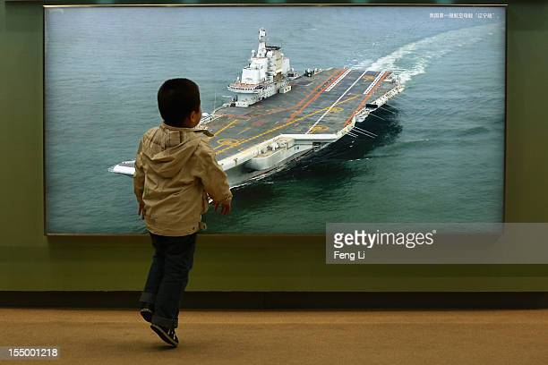 "Chinese little boy passes the photo of China's first aircraft carrier as visiting an exhibition entitled ""Scientific Development and Splendid..."