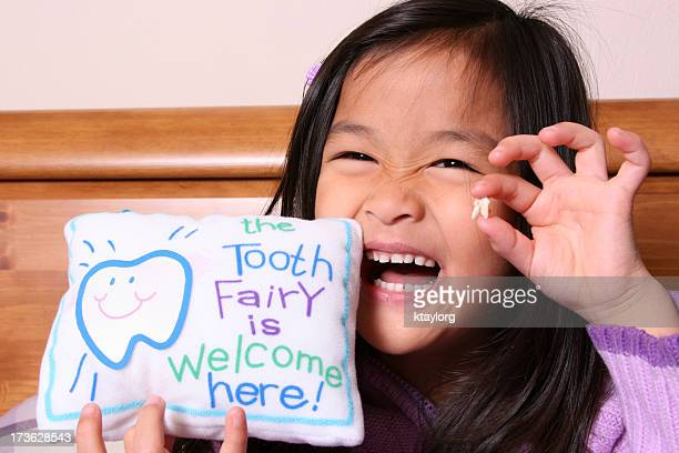 chinese little girl holding up her tooth - tooth fairy stock pictures, royalty-free photos & images