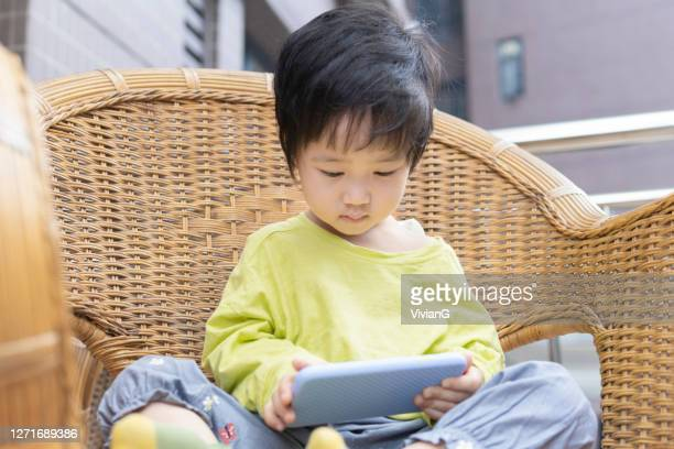 a chinese little girl playing mobile phone on a cane chair on the balcony - school cane stock pictures, royalty-free photos & images