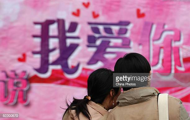"Chinese lovers walk past a giant billboard with Chinese characters reading ""I love you"" on Valentine's Day February 14, 2005 in Beijing, China...."