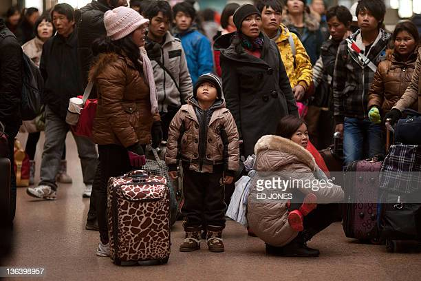 Chinese Lunar New Year travellers check train times at a station in Beijing on January 4 2012 The weeklong holiday also known as the Spring Festival...