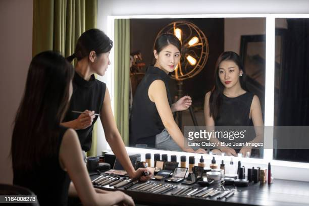 chinese makeup artist applying makeup on model - coulisses photos et images de collection