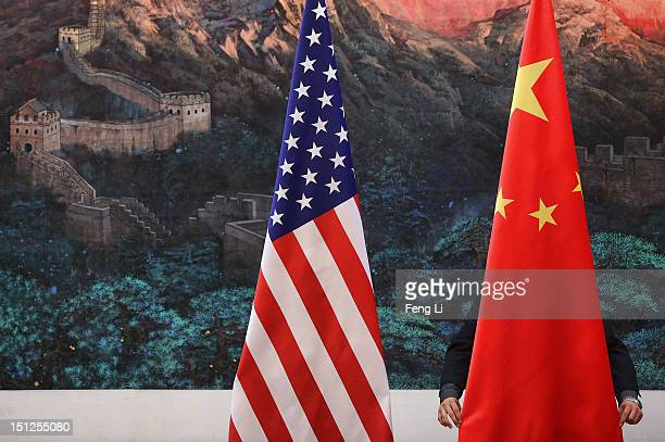 Chinese man adjusts a Chinese flag before Chinese Foreign Minister Yang Jiechi and US Secretary of State Hillary Clinton's press conference at the...