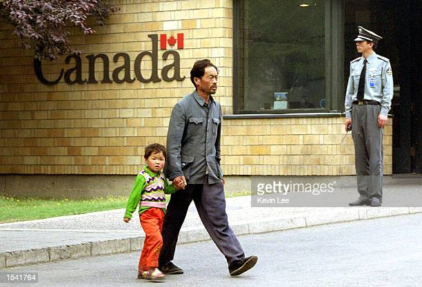 Chinese man and a child pass by the front door of the Canadian Embassy May 13 2002 in Beijing China Two North Korean asylum seekers slipped into the...