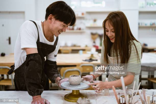 a chinese man and a chinese woman are in a studio making pottery - 僅成年人 個照片及圖片檔