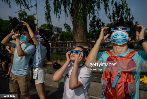 Chinese man and girl wear protective masks to prevent COVID-19 and protective glasses as they watch the sun during the annular solar eclipse outside...