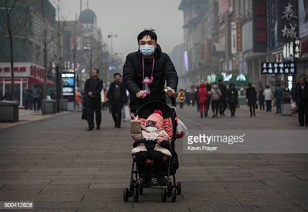 Chinese man and his child wear masks to protest against pollution as they walk through a shopping area in heavy smog on December 8 2015 in Beijing...