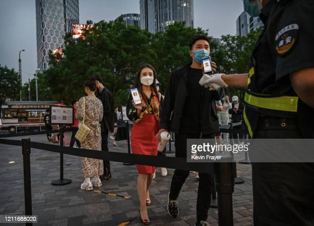 Chinese man and woman show their local health QR codes from the Beijing Municipality to a security guard as he checks her temperature before entering...
