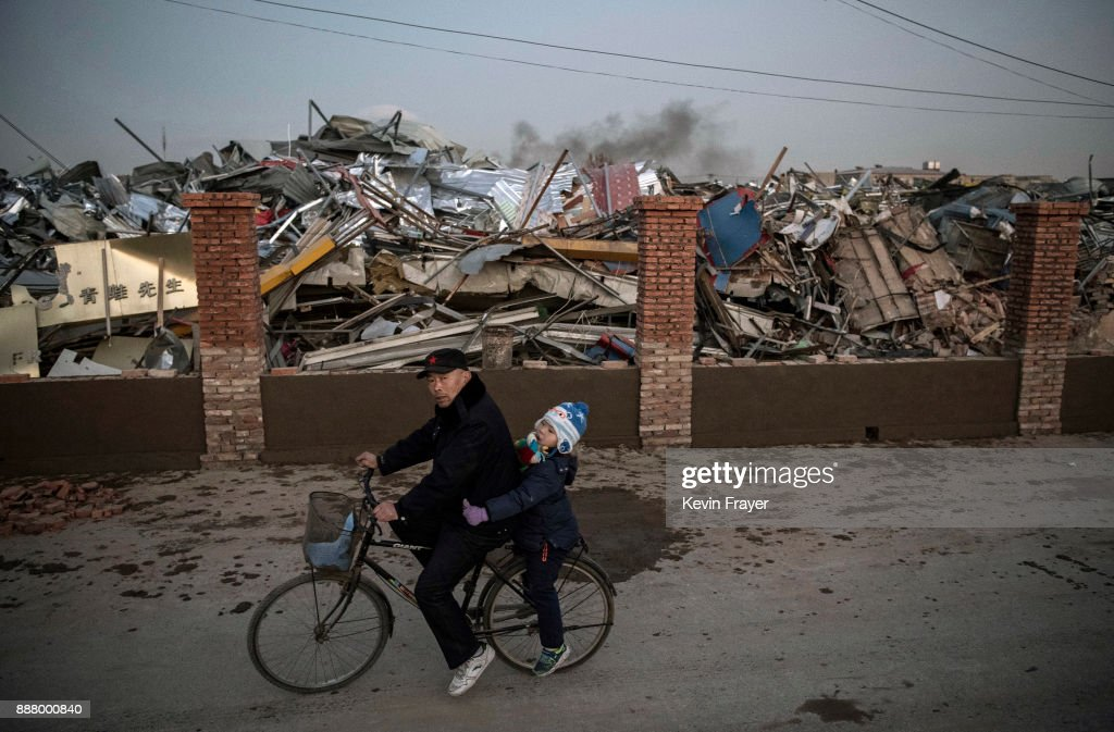 A Chinese man and young girl ride by buildings demolished by authorities in an area that used to have migrant housing and factories on December 6, 2017 in the Daxing District of Beijing, China. Thousands of migrant workers have been forcibly evicted in recent weeks in a sweeping government safety campaign following a deadly fire at a housing settlement. Many migrants, who came to Beijing from poor rural areas to find employment, say they were given little notice to leave and cannot afford to move somewhere else. The government's plan to demolish the buildings was actually announced in a 2015 strategy to reduce and cap the capital's population, but the mass evictions were accelerated after the fire and have stirred public backlash. The migrant population typically work in jobs such as construction, sanitation, and deliveries that have effectively built Beijing and keep it running. Some companies announced assistance and temporary housing for employees who have been affected, but many migrants say they have little choice but to move back to their hometowns.