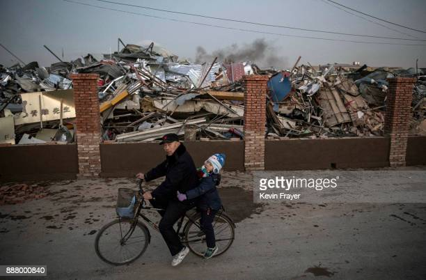 Chinese man and young girl ride by buildings demolished by authorities in an area that used to have migrant housing and factories on December 6 2017...