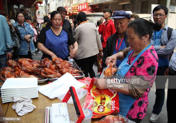 Chinese man buys cheap grilled chicken from a woman vendor who puts the chicken in a platic bag, we are in the market on Qibao Old Street, Beijing,...