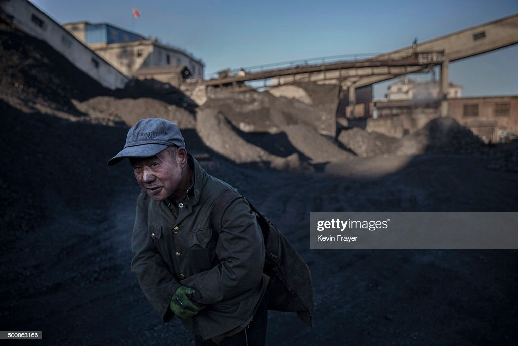 A Chinese man carries coal he collected from a sorting area at a coal mine on November 25, 2015 in Shanxi, China. A history of heavy dependence on burning coal for energy has made China the source of nearly a third of the world's total carbon dioxide (CO2) emissions, the toxic pollutants widely cited by scientists and environmentalists as the primary cause of global warming. China's government has publicly set 2030 as a deadline to reach the country's emissions peak, and data suggest the country's coal consumption is already in decline.