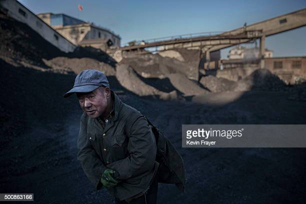 A Chinese man carries coal he collected from a sorting area at a coal mine on November 25 2015 in Shanxi China A history of heavy dependence on...