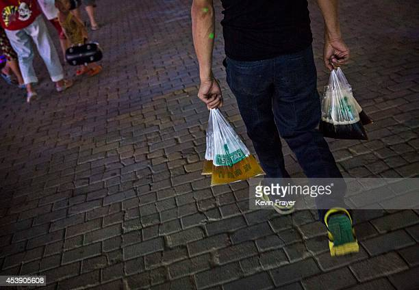Chinese man carries plastic bags of Tsingtao beer from a concession during the 24th Annual Qingdao International Beer Festival on August 20 2014 in...