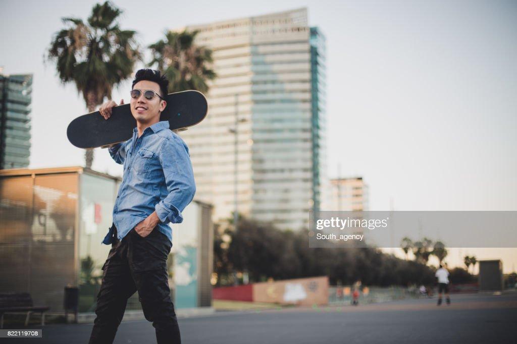 Chinese man carrying skateboard : Stock Photo