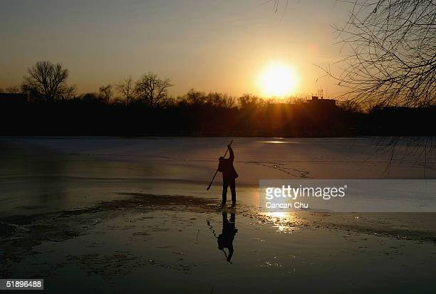Chinese man clears some ice from Shishahai Lake for swimming December 27 2004 in Beijing China The lake is a popular spot for people who love winter...