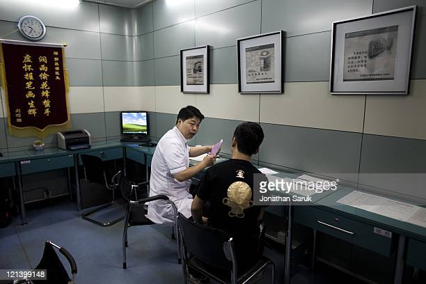 Chinese man consults a surgeon before undergoing a rhinoplasty procedure at the Shisanba Cosmetic Surgery Hospital May 12 2011 in Beijing China The...