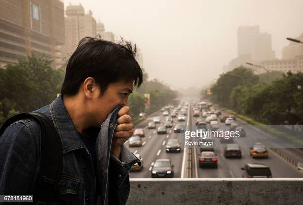 Chinese man covers his mouth and nose with his jacket to try and protect from particles blown in during a sandstorm as he walks in the street on May...