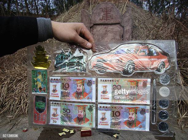 Chinese man displays paper presents including paper cars paper houses paper mobile phones and paper credit cards to be burned in front of a tomb...
