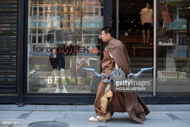 A Chinese man dressed as a warrior cartoon character walks outside a shopping mall in Beijing on July 6 2018 The US is set to begin enforcing tariffs...
