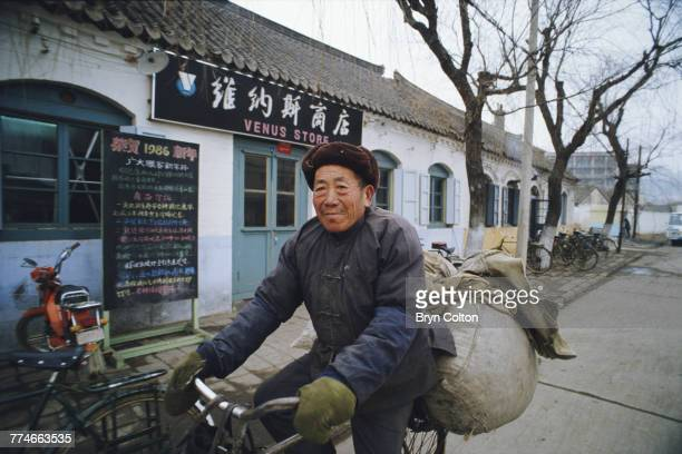 A Chinese man dressed in a fur hat green gloves and winter clothes rides his bicycle along a street past the Venus Store in the city of Weihai in...
