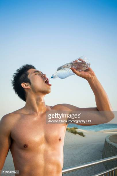 Chinese man drinking from water bottle at waterfront