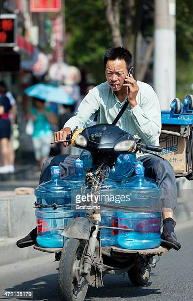 Chinese man driving motorbike transporting water