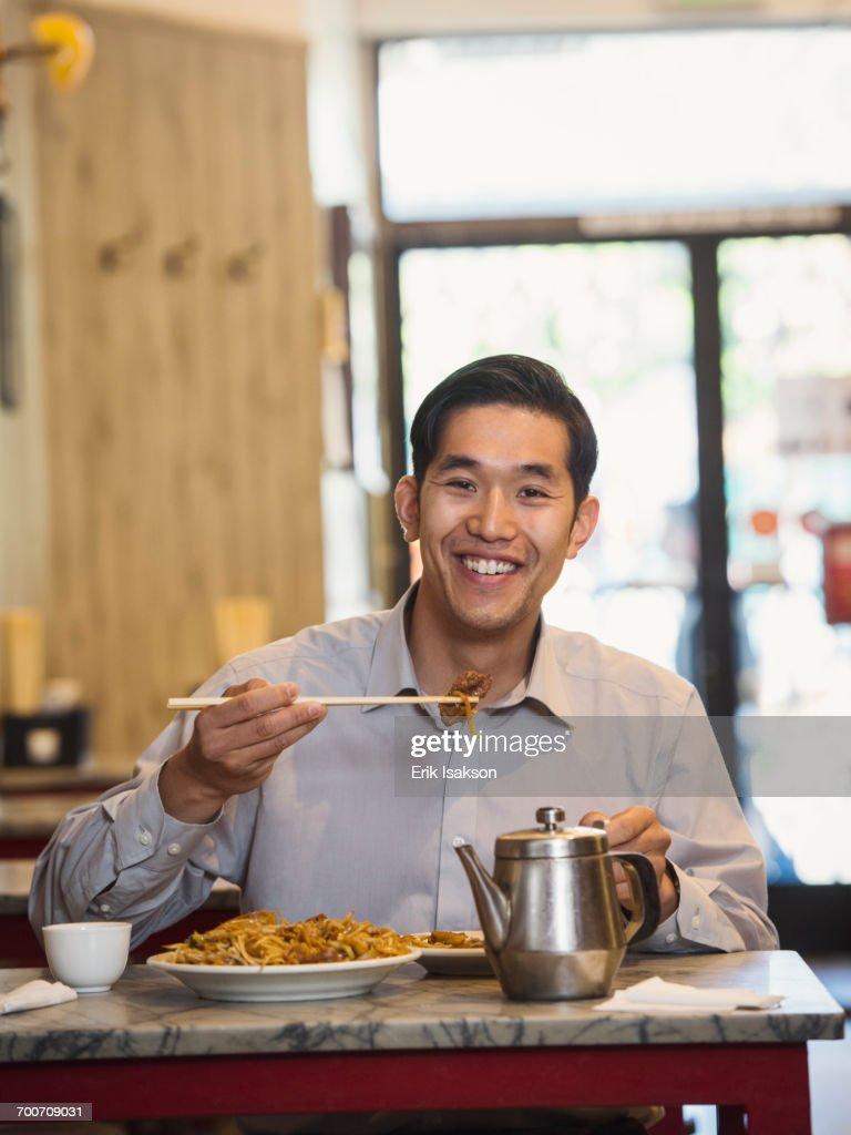 Chinese man eating with chopsticks in restaurant : ストックフォト