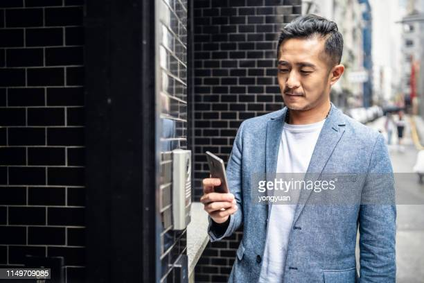chinese man entering his home with his smartphone - smart stock pictures, royalty-free photos & images