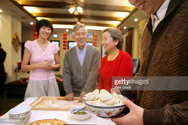 Chinese man filling Chinese dumplings in a bowl on New Years Eve