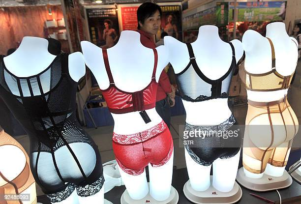 A Chinese man gazes at the mannequins with the latest women undergarments at a beauty fair in Wuhan central China's Hubei province on October 17 2009...