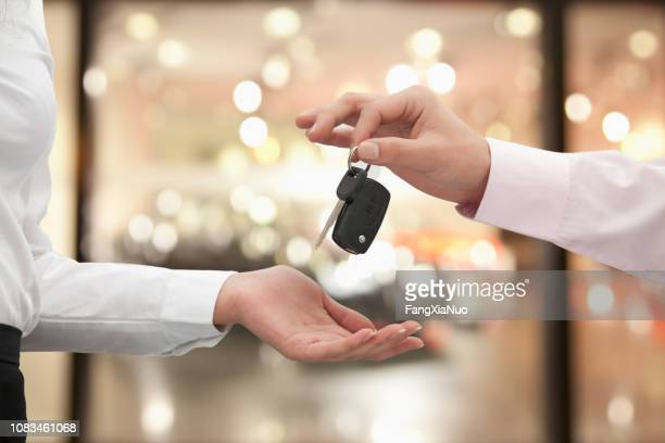 chinese man handing woman car key - car key stock pictures, royalty-free photos & images