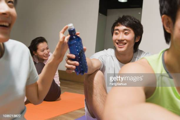 chinese man handing woman water bottle in exercise class - passing sport foto e immagini stock