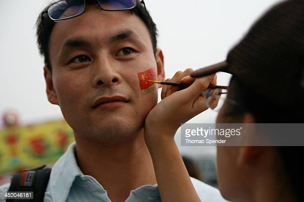 Chinese man has a Chinese flag painted on his face outside the venue for the Beijing Olympics.