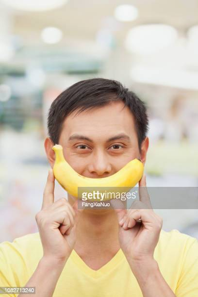 banane holding homme chinois - content photos et images de collection