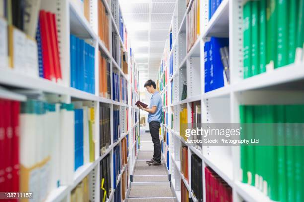 chinese man holding book in library - post secondary education stock pictures, royalty-free photos & images
