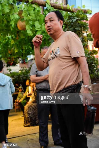 chinese man holding toothpick in a pedestrian street in urumqi - sergio amiti stock pictures, royalty-free photos & images