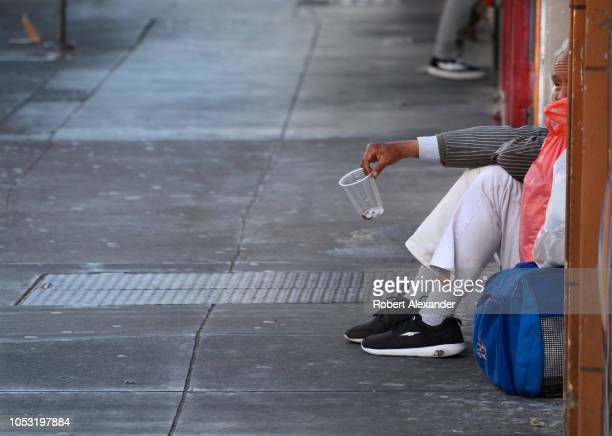 Chinese man in San Francisco California's Chinatown district sits beside a sidewalk with a cup in his extended hand hoping people passing by will...