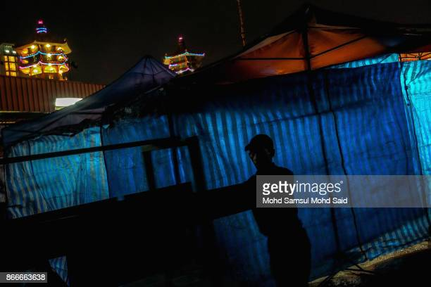 Chinese man is seen in sillhoutted as he works with joss stick trail during The Nine Emperor Gods Festival inside the temple on October 26 2017 in...