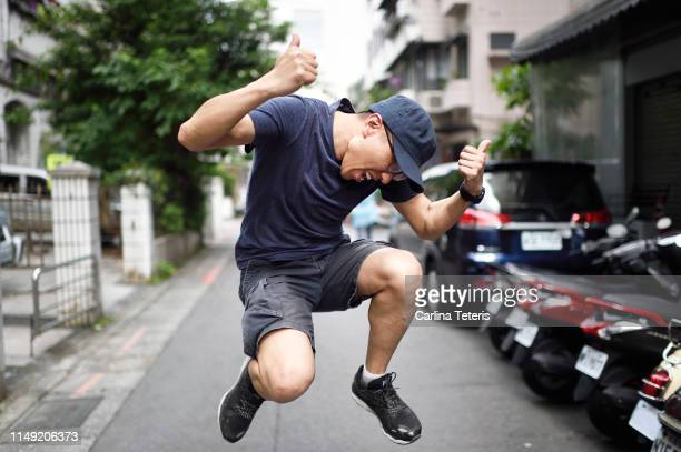 chinese man jumping for joy in the street - extatisch stockfoto's en -beelden