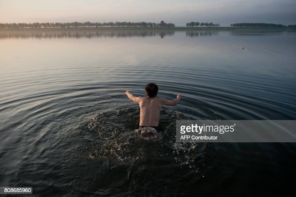 A Chinese man jumps in the water for his routine morning swim exercise next to the Friendship bridge on the Yalu River connecting the North Korean...