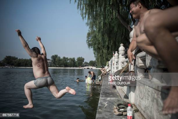 A Chinese man jumps to cool off in the historic Houhai Lake in Beijing on June 19 2017 The manmade lake which was created more than 700 years ago...
