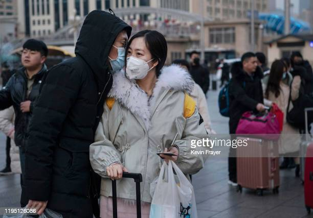 Chinese man kisses his partner goodbye while both wear protective masks as she leaves to travel home at Beijing Railway station before the annual...