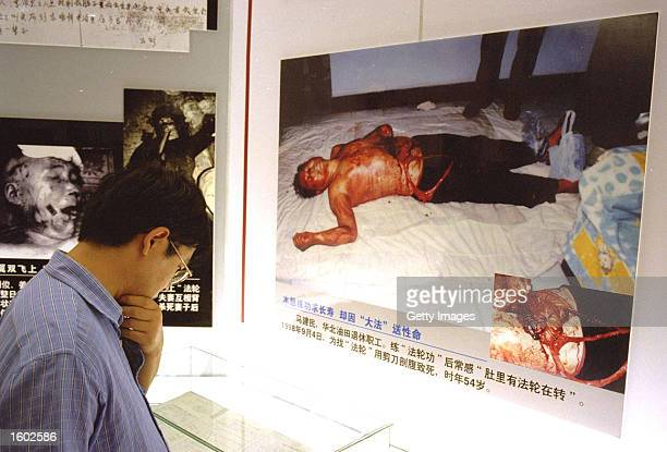 Chinese man looks at a display of images organisers describe as showing deceased members of the Falun Gong sect in an anticult exhibition July 19...