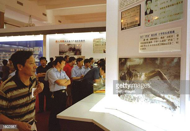Chinese man looks at a display of images organisers describe as showing deceased members of the Falun Gong sect in an anti-cult exhibition July 19,...